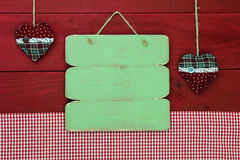 Blank antique green wooden menu sign with holiday hearts and red gingham tablecloth Royalty Free Stock Images