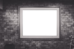Blank antique picture frame on brick wall, vignetting around (bl Stock Photos