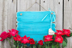 Blank antique teal blue sign with red flower border and wooden hearts hanging on wood background Royalty Free Stock Images