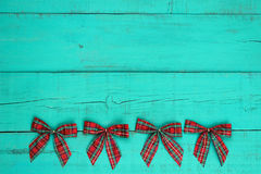 Blank antique teal blue weathered wooden wall with red plaid Christmas bow border Royalty Free Stock Photo