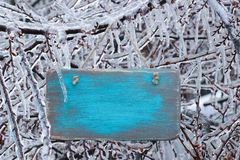 Blank antique teal blue wooden sign hanging on ice covered tree branches royalty free stock photo