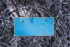 Blank antique wooden sign hanging on ice covered tree branches stock photography