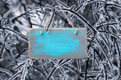 Blank antique wooden sign with ice covered tree branches in background stock photo