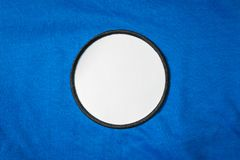 Blank arm patch on blue sport shirt. White team logo and emblem for your montage or edit. Blank arm patch on blue sport shirt. White team logo and emblem for royalty free stock photo