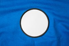 Blank arm patch on blue sport shirt. White team logo and emblem for your montage or edit. Logo royalty free stock image