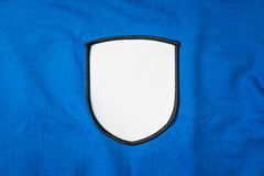 Blank arm patch on blue sport shirt. White team logo and emblem for your montage or edit. Logo royalty free stock photography