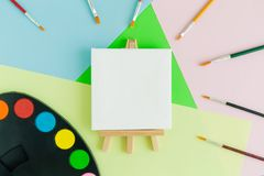 Blank art canvas on easel with multicolored paint brushes and art palette on pastel background. Flat lay of art canvas on easel with art palette and paintbrushes stock photography