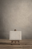 Blank Art Canvas on Wooden Easel against Empty Wall with Planked Stock Image