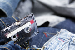 Audio Cassette on Denim. A blank audio cassette laid on the background of various pairs of jeans pants. Very shallow depth of field stock image