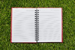 Blank background. paper spiral notebook on grass Stock Photos