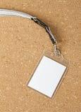 Blank badge with neckband on corkboard background. Stock Image