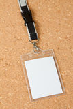 Blank badge with neckband on corkboard background. Royalty Free Stock Images