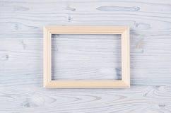 Blank beige wood frame on light blue wooden board. Copy space, top view. Blank beige wood frame light blue wooden board. Copy space, top view stock image