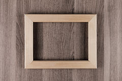 Blank beige  wooden frame on brown surface board, mock up, top view. Royalty Free Stock Photography