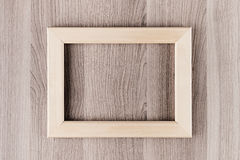 Blank beige  wooden frame on brown surface board, mock up, top view. Royalty Free Stock Images