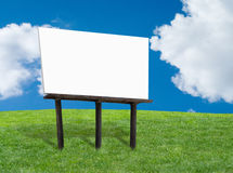 Blank billboard. Blank white billboard on a green grassy hill with blue cloudy sky stock photography