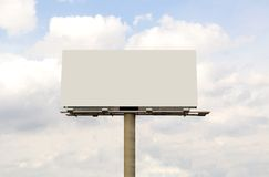 Blank Billboard. Blank white billboard with a blue sky background and white puffy clouds. Billboard has a long pole which can be duplicated to make the outdoor stock photography