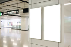 Blank billboard. Two big vertical / portrait orientation blank billboard on modern white wall with subway concourse background stock image