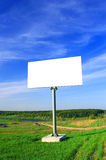 Blank billboard. On the green field and blue sky Stock Image