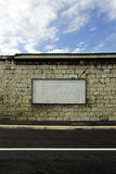 Blank billboard. Large white blank billboard on the stone wall by the street stock photo