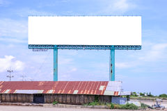Blank billboard behind rustty roof of salt shed with blue sky for advertising. Stock Photos