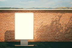 Blank billboard brick. White billboard standing next to red brick wall with landspace in the background. Mock up, 3D Rendering Stock Image
