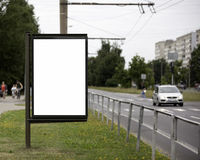 Blank Billboard on City Street. Transport and people in the background Royalty Free Stock Images