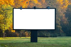 Blank billboard with copyspace surrounded by forest outdoors in. The street side. Large empty template isolated. Leaves, trees, forest background royalty free stock photography