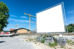 Blank billboard in front of construction area. With cranes stock image