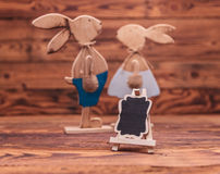 Blank billboard in front of a wooden easter bunnies Royalty Free Stock Photo