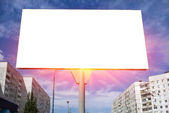 Blank billboard glowing rays on a blue sky at sunset. Stock Photos