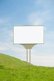 Blank billboard on green hill against blue sky for your advertisement Stock Photography