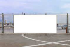 Blank billboard on the harbor fence. A blank billboard ready for new advertising on the harbor fence, big copy space royalty free stock photo