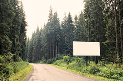 Blank billboard on highway. Blank billboard sign by empty highway through forest mountains landscape. Ad panel on road. Forest road with white billboard for your Stock Photo
