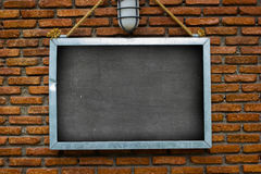 Blank billboard hung on a buildings exterior brick wall, dark to Stock Photography