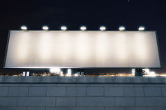 Blank billboard with lights on the top of brick wall at night ci Royalty Free Stock Photography