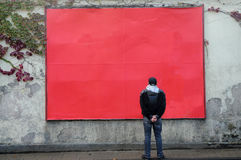 Blank billboard. Man looks at of a blank red billboard royalty free stock photo
