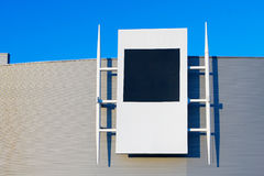 Blank billboard on modern shopping center. Modern building with billboard with blank space for text. Blue sky Stock Image