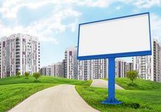 Blank billboard by road running through green Stock Photos