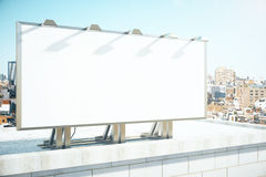 Blank billboard on the roof of building at megapolis city backgr Royalty Free Stock Images