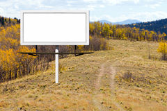 Blank Billboard Sign Along Dirt Trail in Mountains Royalty Free Stock Photo