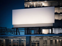 Blank billboard standing on a office building at night. 3d rendering Royalty Free Stock Images