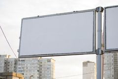 Blank billboard on the street. Empty billboard on the background of houses royalty free stock photography