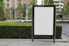 Blank billboard in the street. Green plants stock photo