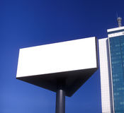 Blank billboard taken against a blue sky. Blank billboard taken against a brilliant blue sky and high rise Stock Photography