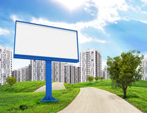 Blank billboard and tree by road running through Stock Image