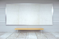 Blank billboard on the wall and wooden bench in empty hall Stock Image