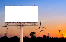 Blank billboard  with wind turbine at sunset time for advertisem Stock Images