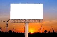 Blank billboard  with wind turbine at sunset time for advertisem Stock Photos