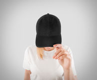 Blank black baseball cap mockup template, wear on women head. Clipping path. Woman in gray hat and t shirt uniform mock up holding visor of caps. Cotton Royalty Free Stock Photos